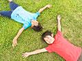 芝生に寝転ぶ子供の写真