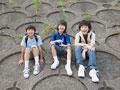 土手に座る小学生の写真