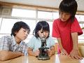顕微鏡を覗く小学生の写真