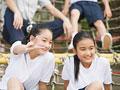 遊具に座る小学生の写真