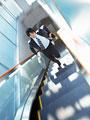 エスカレーターを駆け上がるビジネスマンの写真