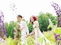花畑を歩く新郎新婦の写真