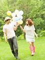 風船を持って歩くカップルの写真
