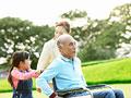 車椅子に乗るシニア男性と家族の写真