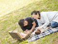 草原でピクニックをする親子の写真