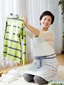 洗濯物を畳む女性の写真