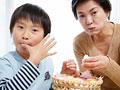 手まり寿司を食べる祖母と孫の写真