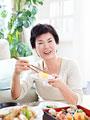 お寿司を食べるシニア女性の写真