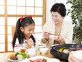 焼き肉を食べる祖母と孫の写真