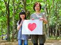 ハートの絵を持つ母と娘の写真