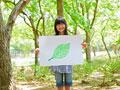 葉の絵を持つ少女の写真