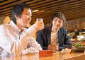 居酒屋で酒を飲む男性たちの写真