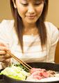 牛すき焼きを食べる女性の写真