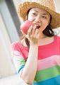 リンゴをかじる女性の写真