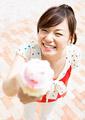 アイスクリームを差し出す女性の写真