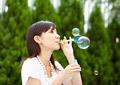 シャボン玉を吹く女性の写真
