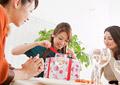 プレゼントを開ける女性の写真