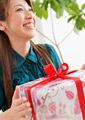 プレゼントを持つ笑顔の女性の写真