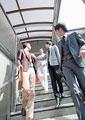 階段を下るビジネスマンとビジネスウーマンの写真