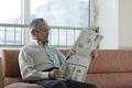 新聞を読むシニアの男性の写真