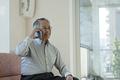 スマートフォンで通話するシニアの男性の写真