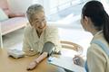 血圧を測るシニアの女性の写真
