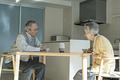 AIスピーカーに話しかける老夫婦の写真