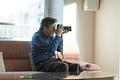 カメラをいじるシニアの男性の写真