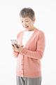 スマートフォンを操作するシニアの女性の写真
