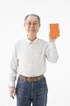 年金手帳を示すシニアの男性の写真