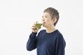 青汁を飲むシニアの女性の写真