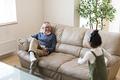 ソファーで孫と遊ぶおじいちゃんの写真