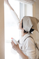窓掃除をする年配の女性の写真