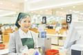 スーパーのレジで働くシニア女性の写真