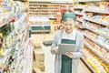 スーパーの在庫を確認するシニア女性の写真